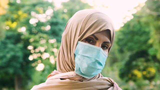 grave donna musulmana mediorientale che guarda la telecamera che indossa una maschera protettiva per il viso - cultura del medio oriente video stock e b–roll
