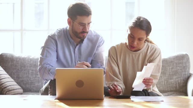 Serious millennial couple calculating domestic bills at home with laptop