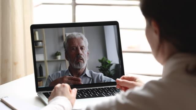 serio vecchio psicologo maschio consulenza cliente femminile tramite webcam chat - didattica a distanza video stock e b–roll