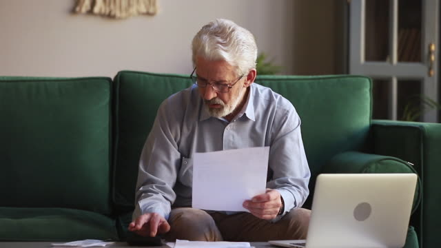 serious old man holding paper calculating domestic bills at home - scontrino video stock e b–roll