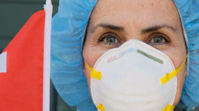 Serious overworked, female matute health care worker holding a French flag