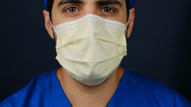 vídeos y material grabado en eventos de stock de trabajador sanitario con exceso de trabajo grave mirando la cámara con una máscara quirúrgica - male nurse