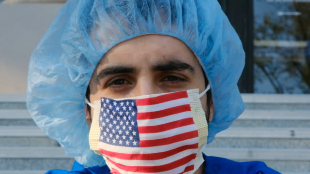 serious overworked, male young health care worker a us flag protective mask looking at the camera - spanish and portuguese ethnicity stock videos & royalty-free footage