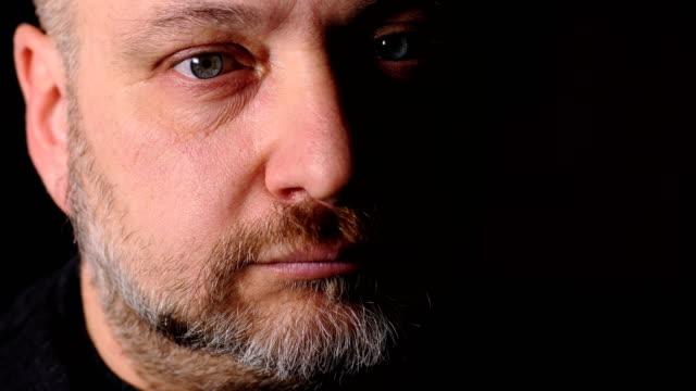 stockvideo's en b-roll-footage met ernstig nadenkend volwassen in het donker zijn ogen openen en de camera kijken - portrait background