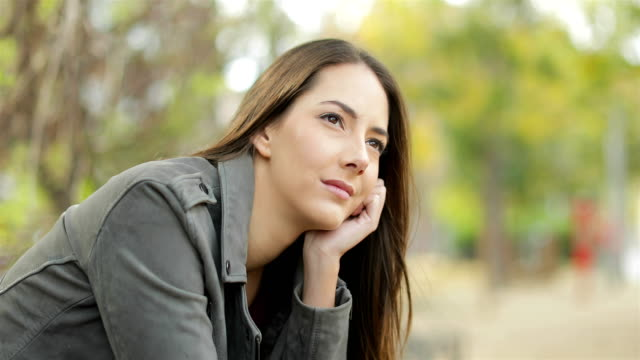 serious pensive woman looking away in a park - cisza filmów i materiałów b-roll