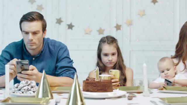allvarliga människor tittar på mobil enhet efter födelsedagsfirande i lyxhus - birthday celebration looking at phone children bildbanksvideor och videomaterial från bakom kulisserna