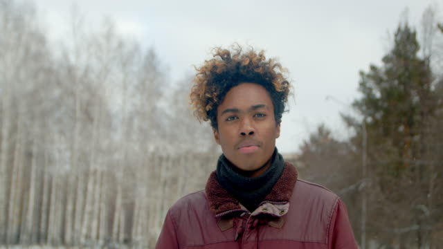 Serious portrait black person closeup african man looking at camera in winter 4K video