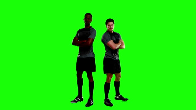 Serious rugby players gesturing in front of camera Serious rugby players gesturing in front of camera on green background sportsperson stock videos & royalty-free footage