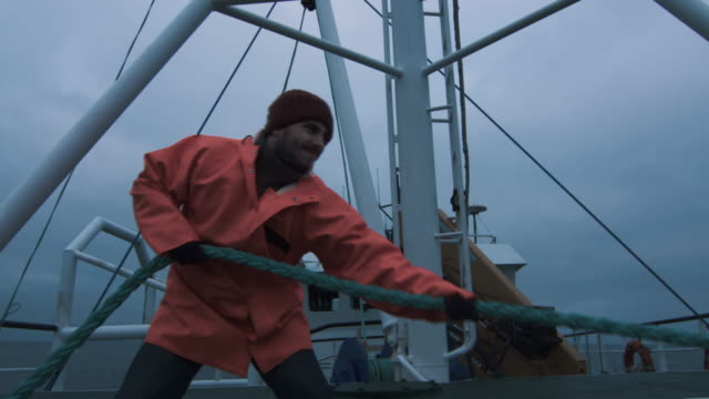 serious seaman pulls the thick rope during traveling on the ship - fishing video stock e b–roll