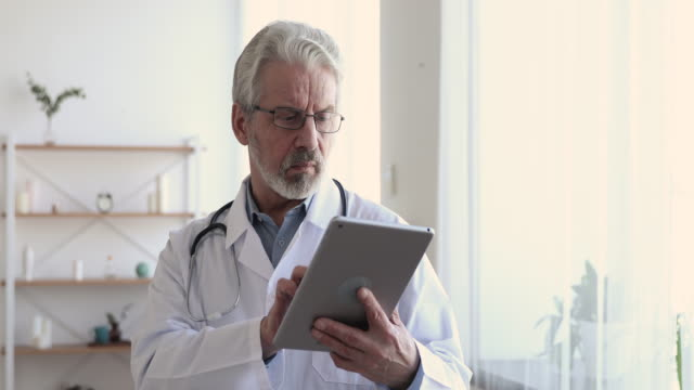 Serious senior adult male doctor using digital tablet at work Serious senior adult male doctor using digital tablet at work. Elderly old professional physician reading online news, checking medical healthcare technology data on pad computer in hospital. general view stock videos & royalty-free footage