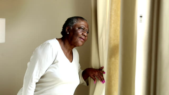 嚴肅的非洲裔美國高級婦女看著窗外 - 看窗外 個影片檔及 b 捲影像