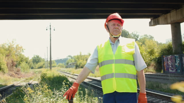 Serious senior engineer in uniform and helmet leans hand and looks on railway video