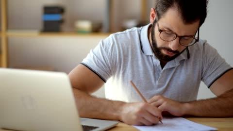 studente serio in occhiali che studia online da casa - imparare video stock e b–roll