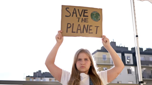 Serious teenage girl stands with her own poster SAVE THE PLANET Serious teenage girl stands with her own poster SAVE THE PLANET. 4K. climate stock videos & royalty-free footage