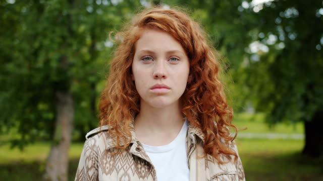 Serious teenager redhead girl looking at camera standing outdoors in park