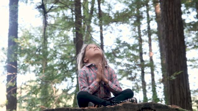 serious thinking little girl praying in the woods - modlić się filmów i materiałów b-roll