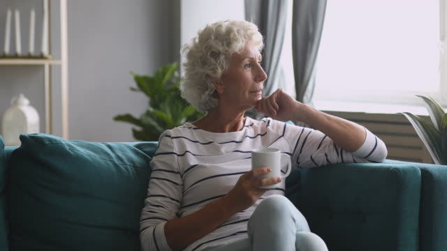 Serious thoughtful old woman looking away drink tea on sofa