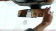 istock Serious woman adjusting rear view mirror. Woman sitting behind steering wheel 1219044927