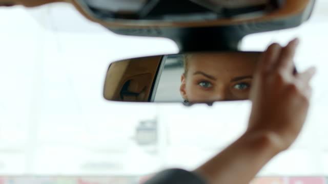 vídeos de stock e filmes b-roll de serious woman adjusting rear view mirror. woman sitting behind steering wheel - espelho