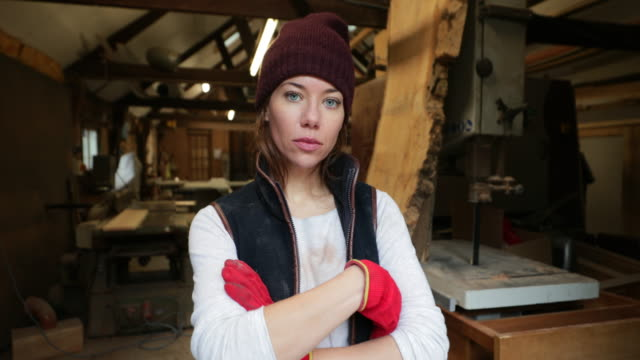 Serious Woman at Work Woman at work in a workshop looking at the camera with a serious expression as she crosses her arms. power tool stock videos & royalty-free footage