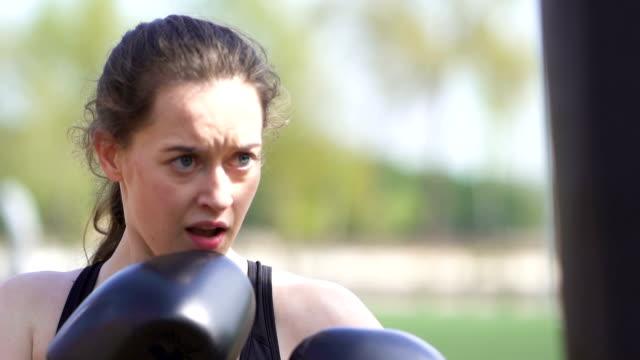 vídeos de stock, filmes e b-roll de mulher séria treinando boxeador com sacos de pancadas no campo de treinamento da cidade de rua. tiro constante, câmera lenta, de perto. - autodefesa