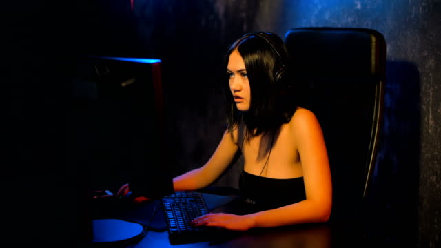 vídeos de stock e filmes b-roll de serious woman gamer playing online game on a pc computer wearing headset and talking with a team using microphone - jogos internacionais