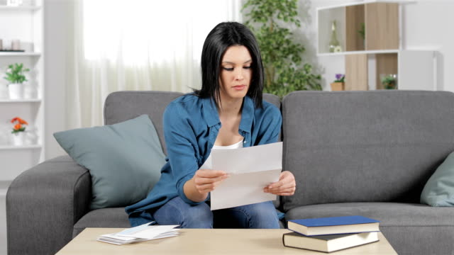 serious woman reading a letter at home - ricevere video stock e b–roll
