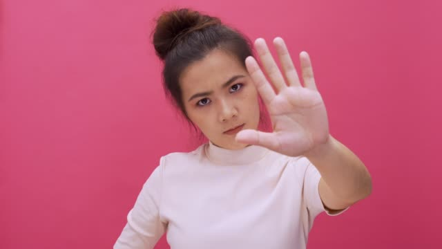 Serious woman waving finger no hand sign look at camera isolated pink background 4k Serious woman waving finger no hand sign look at camera isolated pink background 4k east asian ethnicity stock videos & royalty-free footage