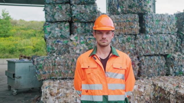 operaio serio in piedi all'aperto presso l'impianto di riciclaggio - sostenibilità video stock e b–roll