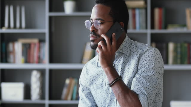 Serious young african ethnic man in glasses talking on smartphone.