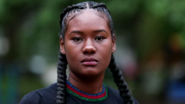 allvarlig ung svart kvinna tittar på kameran utanför. dramatisk afrikansk flicka stirrar betraktaren - etnicitet bildbanksvideor och videomaterial från bakom kulisserna