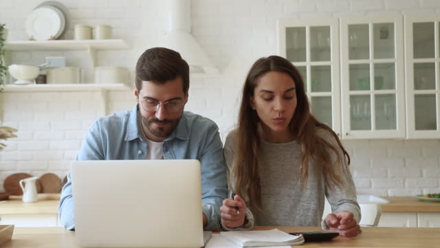 serious young couple paying bills online on website app - bills and taxes stock videos & royalty-free footage