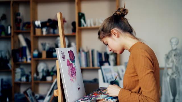 vidéos et rushes de demoiselle sérieuse étudiante en art est fleurs de peinture sur toile en tenant le pinceau et la palette avec les peintures de studio. mode de vie, passe-temps et concept arts visuels. - toile à peindre