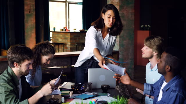 allvarlig ung dam ger handlingar till sina anställda som sitter vid bordet, tittar på papper och talar vid möte i office. lagarbete och management koncept. - liten bildbanksvideor och videomaterial från bakom kulisserna