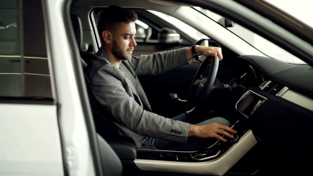 Serious young man is sitting inside new car in motor showroom and checking electronics pressing buttons on control panel touching car parts. Purchasing automobile concept. Serious young man is sitting inside new modern car in motor showroom and checking electronics pressing buttons on control panel touching car parts. Purchasing automobile concept. car salesperson stock videos & royalty-free footage