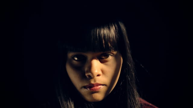 Serious young with blank expression looking at camera. Indoor low key close-up dolly camera 4k video of serious Asian, Indian young woman sitting against dark background at home and side sunlight coming directly trough a window is falling on her face. She is thinking and looking at camera with serious and blank expression. One person, headshot and selective focus with copy space. side lit stock videos & royalty-free footage