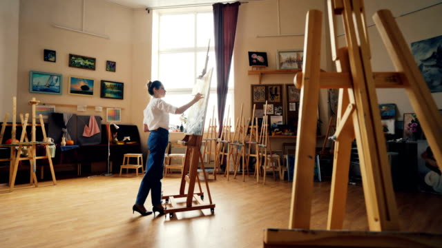 serious young woman artist is working at picture painting with acrylic paints in arts school classroom with easels and artworks. creative work and people concept. - tavolozza video stock e b–roll