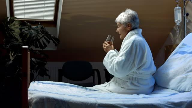 hd dolly: seriously ill senior woman taking pills - age bildbanksvideor och videomaterial från bakom kulisserna