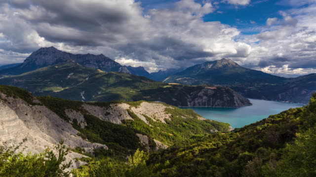 serre-poncon lake and grand morgon peak time lapse in summer. french alps, france - barrage de serre poncon stock videos & royalty-free footage