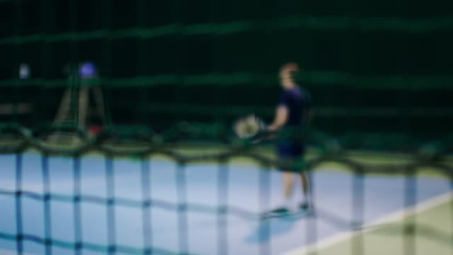 Serve by professional tennis player. Tennis serve indoor of tenis hall. Man on serve with tenis racket and dressed in black t-shirt, black shorts and black shoes video