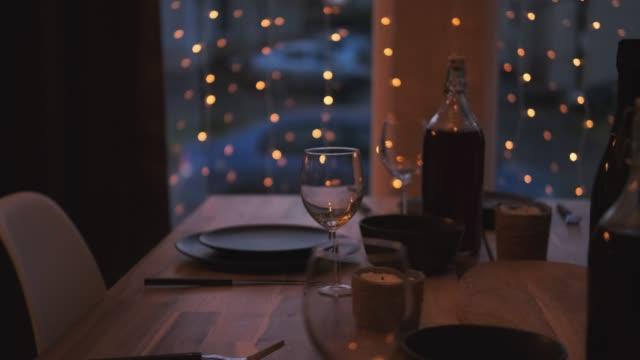 servierter tisch zu hause im wohnzimmer gegen das fenster. abendd eskte licht. girlanden hängen am fenster. vorbereitung auf die feier. - girlande dekoration stock-videos und b-roll-filmmaterial