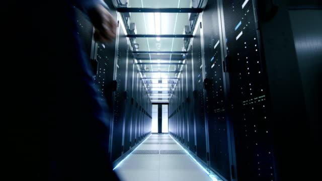 stockvideo's en b-roll-footage met ingenieur van de server in het datacentrum doorloopt schuifdeuren en opent server rack behuizing. - datacenter