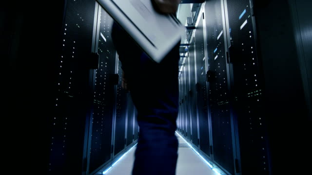 Server Engineer in Data Center Walks Through Sliding Doors and Opens Server Rack Cabinet. video