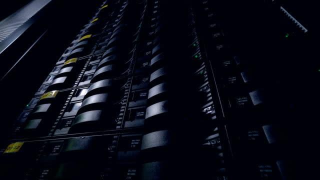 暗闇の中で勤務するネットワーク データ センター サーバー ラックは、ファームをレンダリングします。4 k。 - スーパーコンピューター点の映像素材/bロール