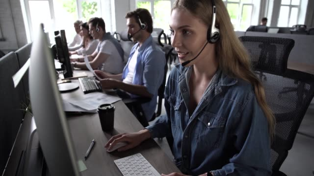 Service phone operators sit at shared desk focus on sales. Agent woman in headset use pc answers incoming calls talk with client provide professional support to customers sell company product concept