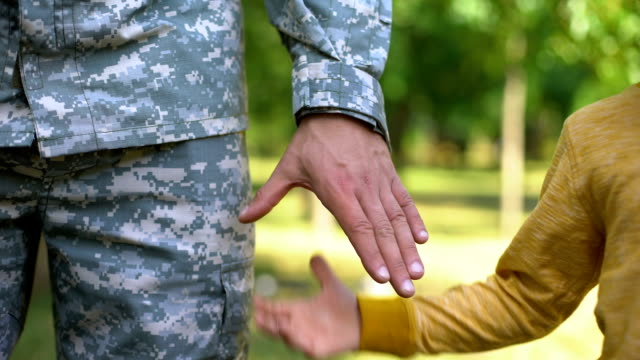 Serviceman holding boys hand, army defending safe future, family togetherness Serviceman holding boys hand, army defending safe future, family togetherness military uniform stock videos & royalty-free footage