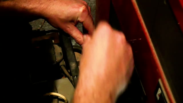 Servicing home gas burner Screwing off gas burner flange screws before unmouting burner from furnace. Doing service on home gas burner heater. In slow motion hd. furnace stock videos & royalty-free footage