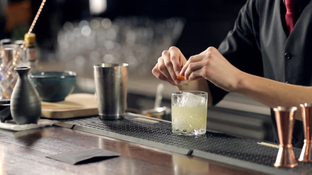 serving a cocktail with a twisted orange peel - bartender стоковые видео и кадры b-roll