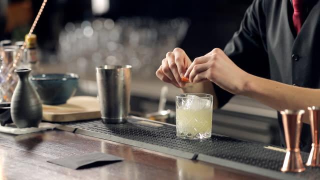 트위스트 오렌지 껍질과 칵테일 제공 - bartender 스톡 비디오 및 b-롤 화면