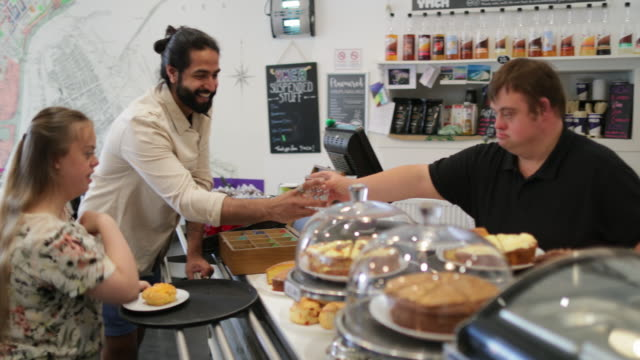 Serving a Scone in a Cafe A young man with Down syndrome is serving customers in the cafe that he work in. persons with disabilities stock videos & royalty-free footage